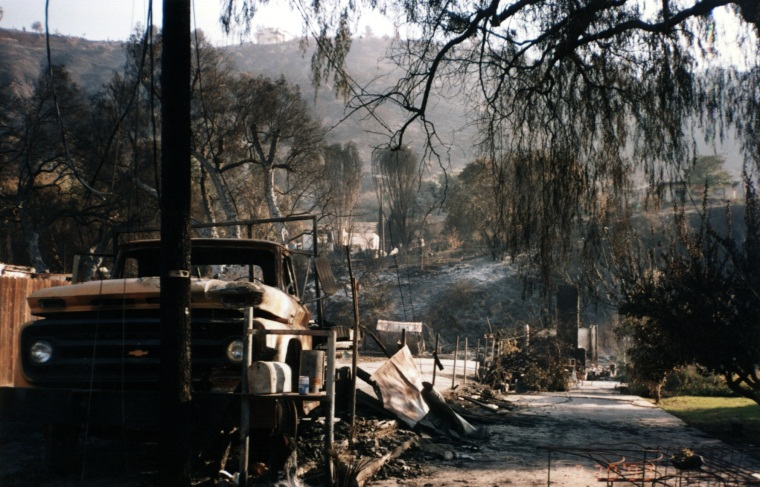 View of fire damaged car and hillside